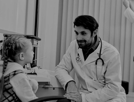 Male doctor talking with child patient while his colleague working in the background