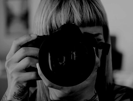 Woman with DSLR camera pointed forward