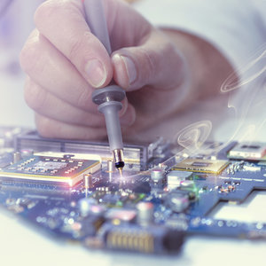 close-up of masculine hand soldering a circuit board