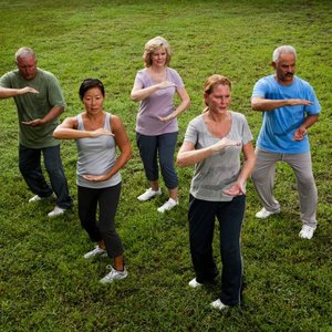 Multi-ethnic group of adults practicing tai chi in park.