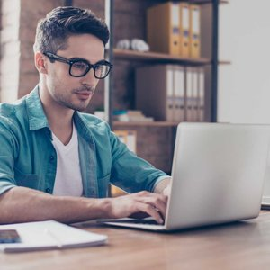 young man with glasses on laptop