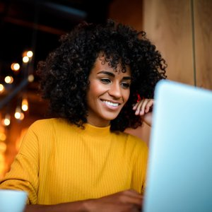 smiling black woman in vibrant yellow sweater using laptop