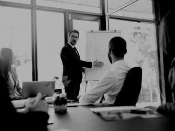 Man presenting business plan on whiteboard to room of coworkers.