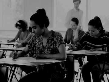 English language students taking an exam in a classroom.