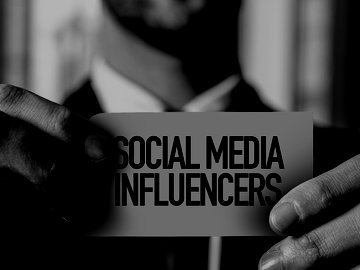 "man holding card with text that reads ""social media influencers"""