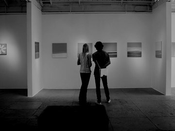 two people looking at paintings in an art gallery
