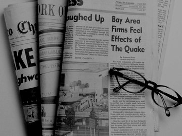 Reading glasses resting on top of newspapers.