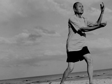 Senior Man Stands on the Beach Doing Tai Chi