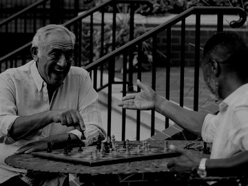 Two male friends playing chess in garden
