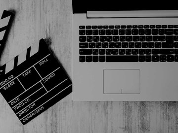 Film clapboard lying next to laptop