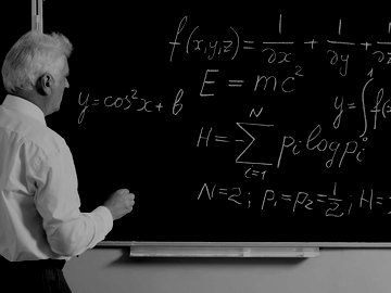 Man working on physics problem on chalkboard
