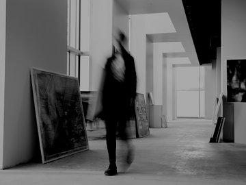 Art Dealer walking with painting in art gallery