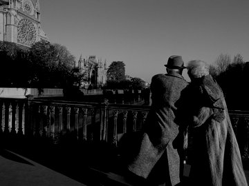 France, Paris, elderly couple walking arm in arm on bridge next to Notre Dame Cathedral