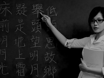 Young woman teaching Chinese scripts and holding a book